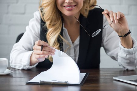 cropped image of businesswoman with clipboard at office