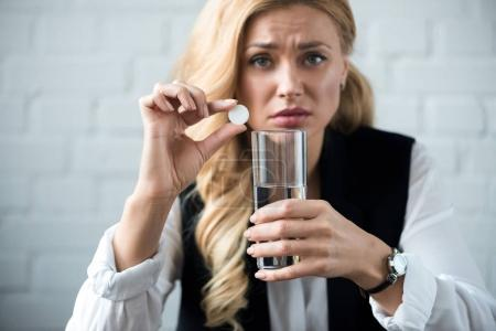 businesswoman holding pill and glass of water and looking at camera