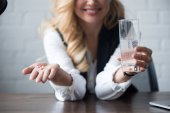 cropped image of happy businesswoman holding pills and glass of water