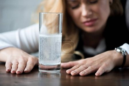 businesswoman with headache sitting near glass of water with medicines