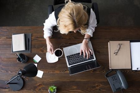 top view of businesswoman using laptop and holding cup of coffee in office