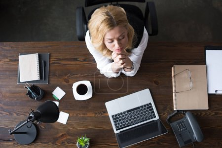 overhead view of businesswoman praying in office
