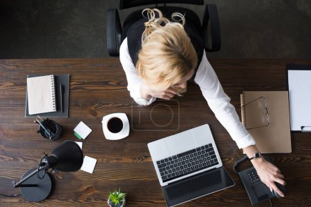 top view of businesswoman taking stationary telephone handset in office