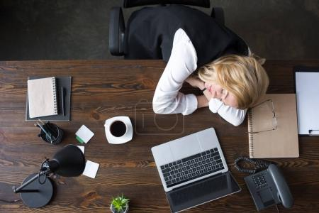 overhead view of businesswoman sleeping at table in office