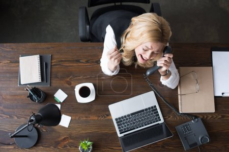 overhead view of happy businesswoman talking by phone and showing yes gesture in office