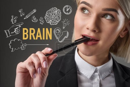 portrait of beautiful young businesswoman with pen and word brain with icons isolated on grey