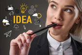 portrait of beautiful young businesswoman with pen and idea icons, isolated on grey