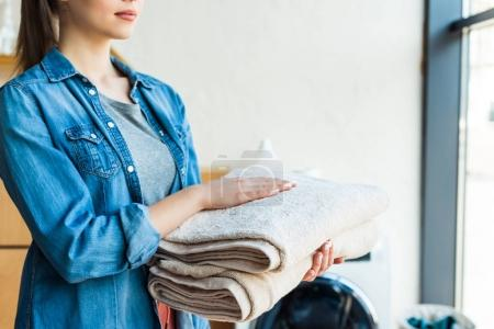 cropped shot of young woman holding clean towels at home