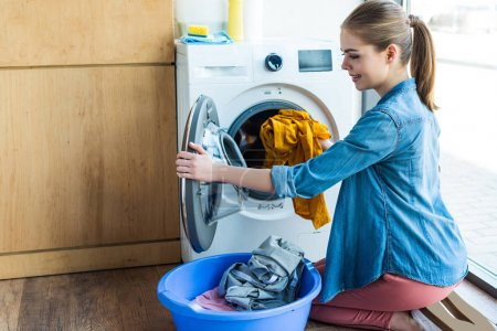smiling young woman taking laundry from washing machine into plastic basin
