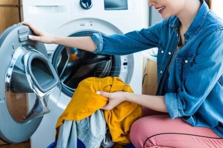 Photo pour Recadrée tir de souriante jeune femme prenant la lessive de la machine à laver - image libre de droit