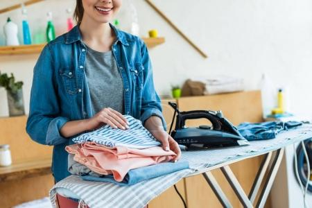 cropped shot of smiling young woman stacking clothes after ironing at home