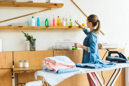 young woman choosing cleaning fluid while ironing clothes at home