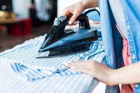 Photo for Close-up partial view of young woman ironing clothes at home - Royalty Free Image