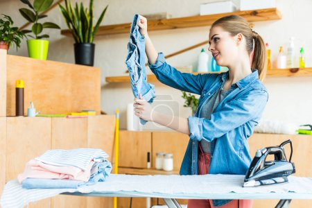 beautiful smiling young woman ironing clothes at home