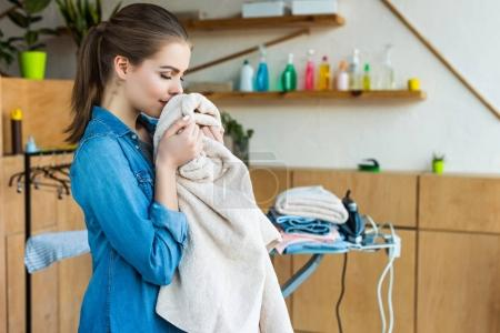 smiling young woman holding towel while ironing clothes at home