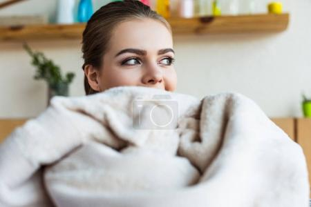 beautiful young woman looking away while holding clean towel