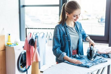 Photo for Beautiful smiling young woman ironing clothes at home - Royalty Free Image