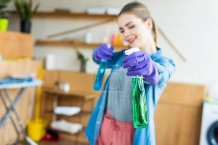 close-up view of smiling young woman in rubber gloves holding spray bottles with cleaning fluids