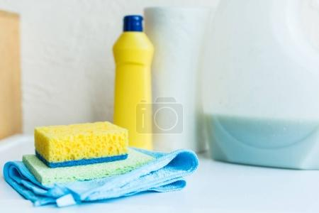 close-up view of towel, sponges and plastic containers with cleaning fluids