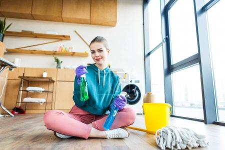 beautiful smiling young woman in rubber gloves holding plastic bottles with cleaning fluids