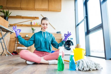 Photo for Smiling young woman sitting on floor and meditating while cleaning house - Royalty Free Image