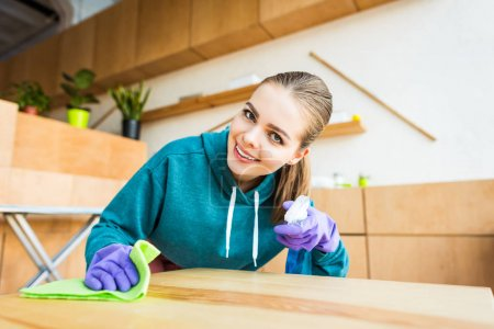 beautiful young woman smiling at camera while cleaning home with rag
