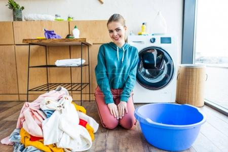 beautiful young woman smiling at camera while kneeling between laundry and plastic basin