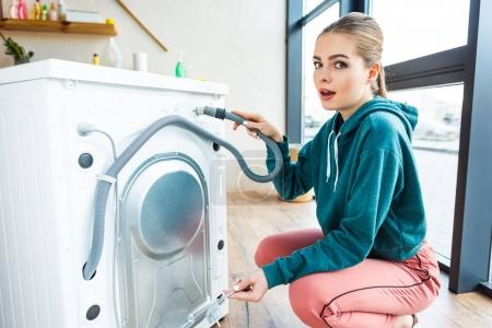 shocked young woman looking at camera while crouching near broken washing machine