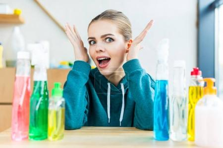shocked young woman looking at camera while sitting at table with plastic bottles with cleaning products