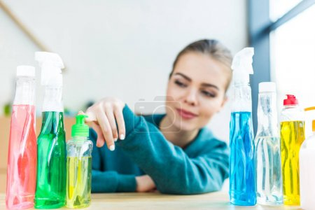 smiling young woman looking at various plastic bottles with cleaning products