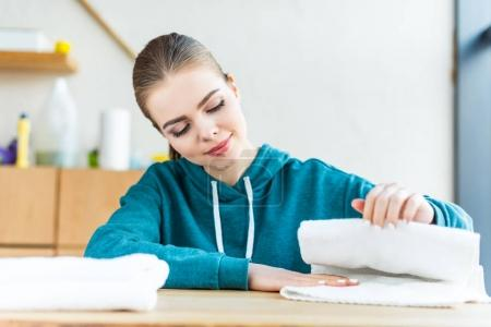 smiling young woman looking at white towels on table