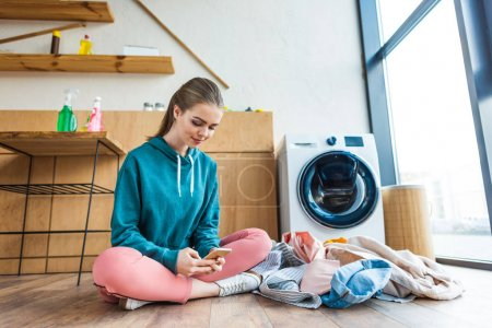 smiling young woman using smartphone while sitting with clothes near washing machine
