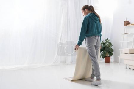 young woman putting yoga mat on floor at home
