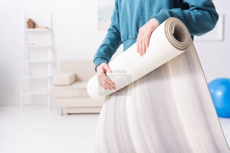 cropped image of girl twisting yoga mat at home