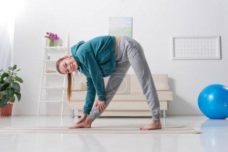girl exercising on yoga mat and looking at camera at home