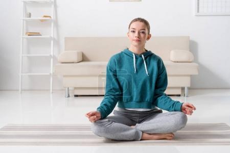 Photo pour Fille assise en position lotus sur tapis de yoga à la maison et regardant la caméra - image libre de droit