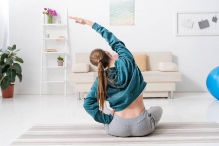 Photo pour Vue arrière de la fille assise en position du lotus et qui s'étend sur le tapis d'yoga à la maison - image libre de droit
