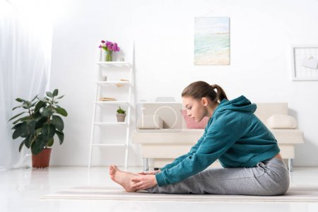 side view of girl exercising on yoga mat at home
