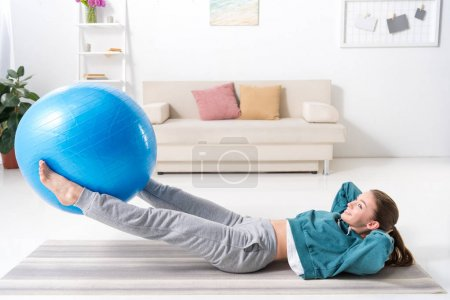 side view of girl doing fitness exercise at home
