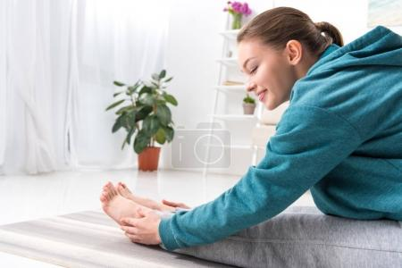 smiling girl stretching on yoga mat at home