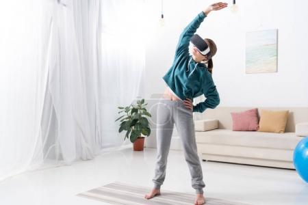 Foto de Chica de pie y estirar con casco de realidad virtual en la estera de la yoga en casa - Imagen libre de derechos