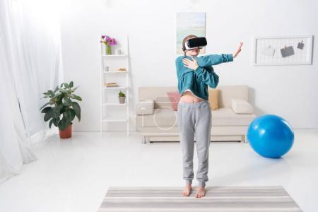 Foto de Chica estirando las manos con casco de realidad virtual en la estera de la yoga en casa - Imagen libre de derechos