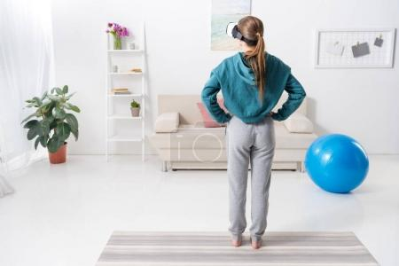 Photo for Rear view of girl exercising with virtual reality headset at home - Royalty Free Image