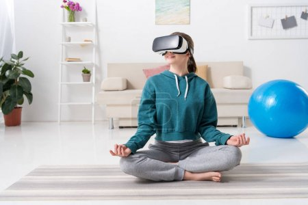 girl sitting in lotus position with virtual reality headset at home