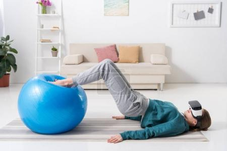 side view of girl exercising with fitness ball and in virtual reality headset at home