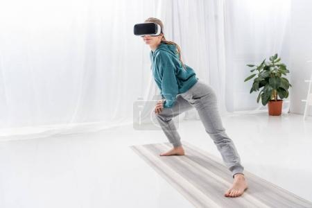 girl stretching legs with vr headset on yoga mat at home