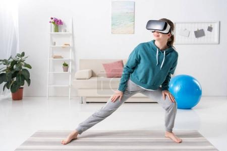 Photo for Girl stretching legs with virtual reality headset on yoga mat at home - Royalty Free Image