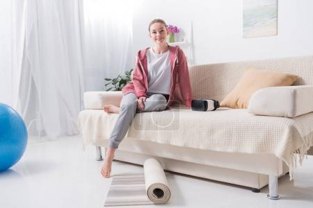 smiling girl sitting on sofa at home and looking at camera