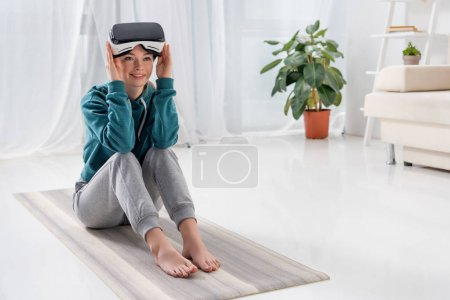 girl sitting on yoga mat with virtual reality headset at home