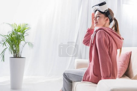 Photo for Side view of girl with virtual reality headset looking away at home - Royalty Free Image